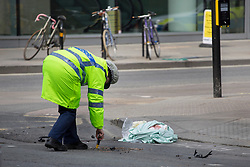 © licensed to London News Pictures. London, UK 08/04/2013. A police officer investigating the scene where a woman cyclist killed on Victoria Street, London in a rush hour collision. Photo credit: Tolga Akmen/LNP