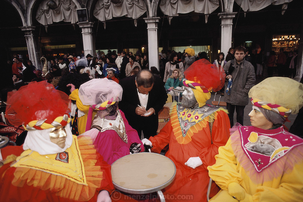 Costumed revelers ordering drinks from a waiter in the  Piazza San Marco, during Winter Carnival in Venice, Italy.