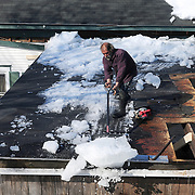 BATH, Maine --  Jeff Patterson of Phippsburg pushes a load of ice from the roof of Lynn Greene's carport roof in Bath on Saturday, after thawing snow damaged the structure on Thursday. Patterson is dismantling the carport at the same time as he removes snow because Greene determined that it was not structurally sound. Photo by Roger S. Duncan for The Forecaster.