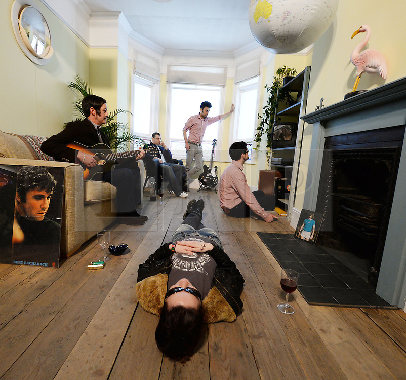 "© Licensed to London News Pictures. 15/04/2014. CITY/TOWN e.g Windsor, UK. Oasis fans recreate the album cover ""Definitely Maybe"" at the Chasing the Sun exhibition, LondonNewcastle Project Space, London. The show, Oasis: Chasing The Sun, celebrates the four years in which the Burnage band went from unsigned act to stadium superstars, and includes original instruments, tour memorabilia, Noel Gallagher's handwritten lyric sheets and pictures from the photoshoots that got their faces on the covers of international magazines.. Photo credit : Mike King/LNP"