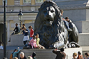 Tourists pose for photographs on lion statue at base of Nelson's Column, Trafalgar Square, London, UK