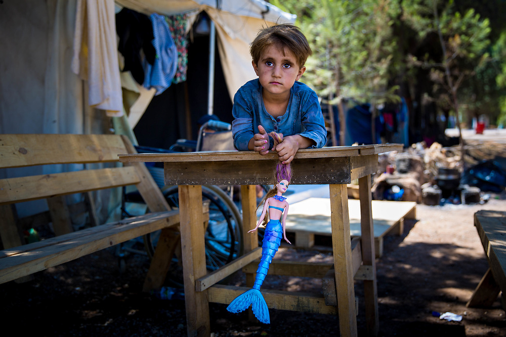 Najah, 4, a Kurdish Syrian refugee from Aleppo, plays on a table her Grandpa Jameel made, which sits outside of her family&rsquo;s tent in Ritsona Refugee Camp, an hour north of Athens, Greece. July 2016.<br />