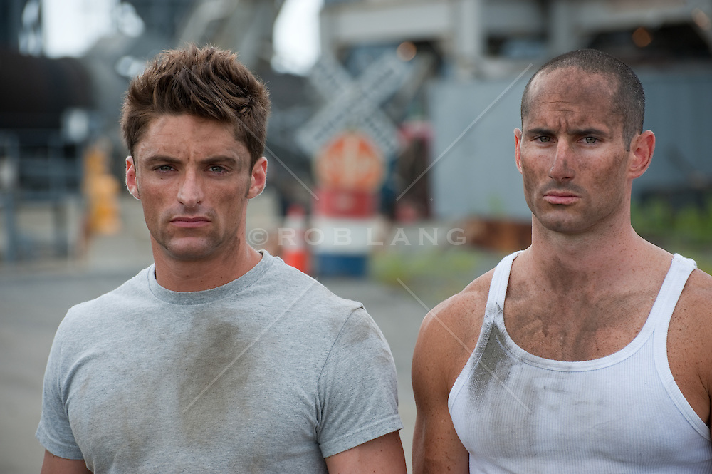 two thirty something men standing outside by an industrial site.  All american men after work staring at the camera. One man wearing a dirty gray tee shirt and the other in a white tank top.  Both men are very serious.
