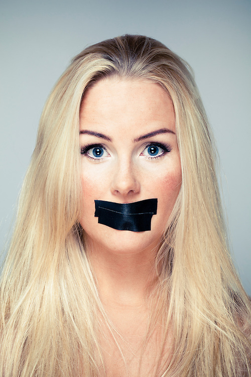 Portrait of a woman with black tape on her mouth