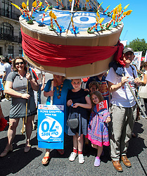 © Licensed to London News Pictures. 30/06/2018. London, UK. People shelter from the sun underneath a 70th anniversary cake as thousands of people take part in a march through central London to mark the 70th anniversary of the NHS. The UK's National Health Service was launched on July 5th, 1948 as part of major social reforms following the Second World War. Photo credit: Ben Cawthra/LNP