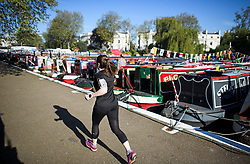 © Licensed to London News Pictures. 05/05/2018. London, UK. A jogger makes her way along the canal towpath during the Canalway Cavalcade festival in Little Venice, West London on Saturday,  May 5th 2018. Inland Waterways Association's annual gathering of canal boats brings around 130 decorated boats together in Little Venice's canals on May bank holiday weekend. Photo credit: Ben Cawthra/LNP