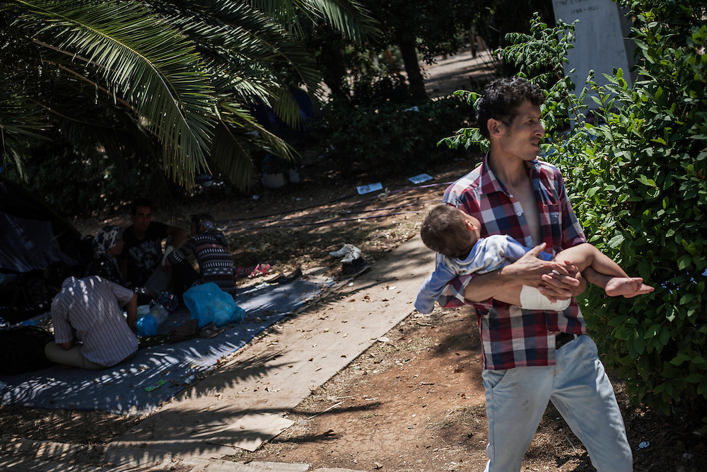 Greece, Athens, July 25th 2015 - A man is carrying his baby at Pedion tou Areos park where hundreds of migrants and refugees mostly from Afghanistan have build a temporary camp, after they arrived in Athens from the Greek islands wishing to continue their journey to central Europe.
