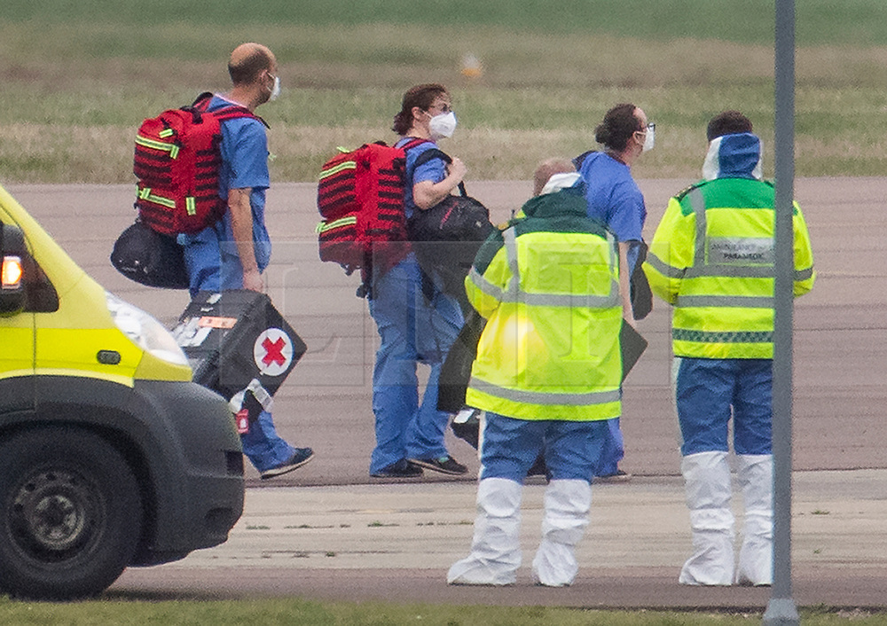 © Licensed to London News Pictures. 31/01/2020. Brize Norton, UK. Paramedics (R) look on a s other medical staff disembark from a charter plane at RAF Brize Norton after being evacuated from Wuhan, China. The flight, carrying 83 Britons and 27 foreign nationals from the centre of the coronavirus outbreak, was initially delayed because of a lack of clearance by Chinese Authorities. The British passengers will travel by coach to a hospital in the north west of England for 14 days quarantine. Photo credit: Peter Macdiarmid/LNP