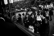 Commuters chat as they wait for their bus in Chongqing.