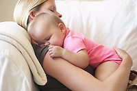 Mother with baby sleeping on sofa