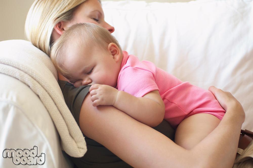 Mother with baby sleeping on sofa