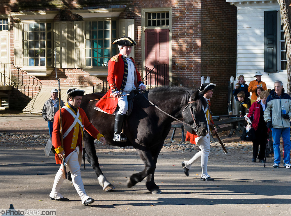 """Actors play a British redcoat foot soldier and officer on a horse, on Duke of Gloucester Street in Colonial Williamsburg, Virginia. People of the 1700's may actually have used the terms """"Regulars"""" or """"the King's men"""" instead of """"redcoats"""", a term which didn't appear commonly in literature until the 1880's. Colonial Williamsburg is the historic district of the independent city of Williamsburg, Virginia, which was colonial Virginia's capital from 1699 to 1780, and a center of education and culture. The Historic Area exhibits actors in period character & costume, colonial houses and American Revolutionary War history."""