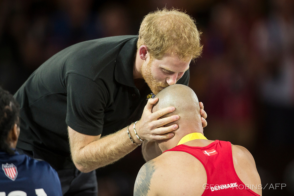 Prince Harry kiss the head of wheelchair rugby gold medalist Maurice Manuel of Denmark at the Invictus Games in Toronto, Ontario, September 28, 2017.