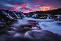 Dramatic lenticular clouds at sunset over Bruarfoss, Iceland