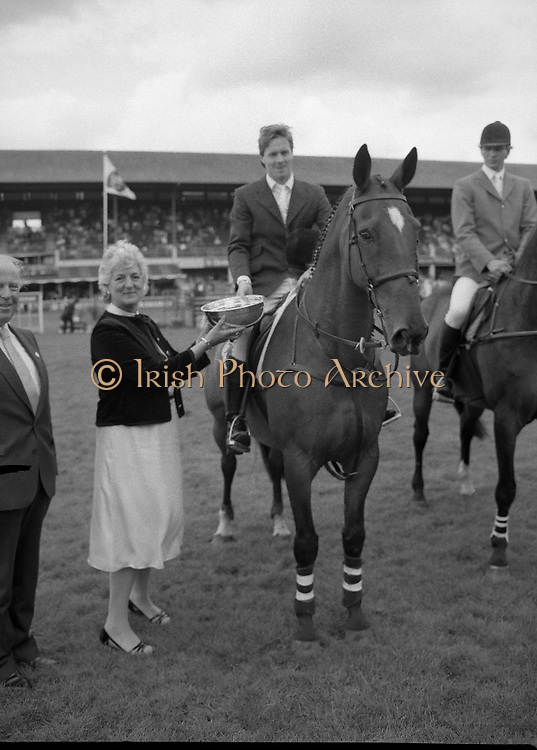 "Shell Puissance Competition R.D.S..1985..07.08.1985..08.07.1985..7th August 1985..The Shell sponsored Puissance was held in the R.D.S.Dublin during Dublin Horse Show week..Image shows Mrs Olga Beveridge,wife of the Managing Director of irish Shell Ltd,.presenting the winners trophy to Mr Trevor Coyle. Mr Coyle won aboard his mount ""Bank Strike"".Mr Beveridge is pictured alongside his wife."