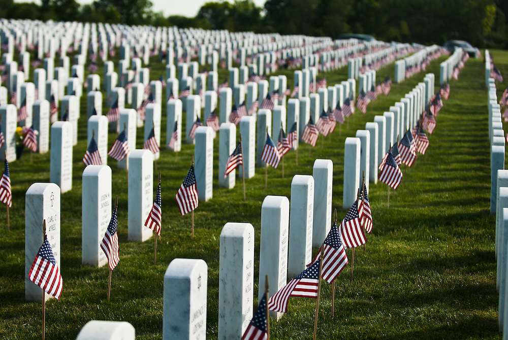 Lathan Goumas | MLive.com..Miniature American flags sit in front of a headstones at the Great Lakes National Cemetery in Holly, Mich. on Friday May 25, 2012.