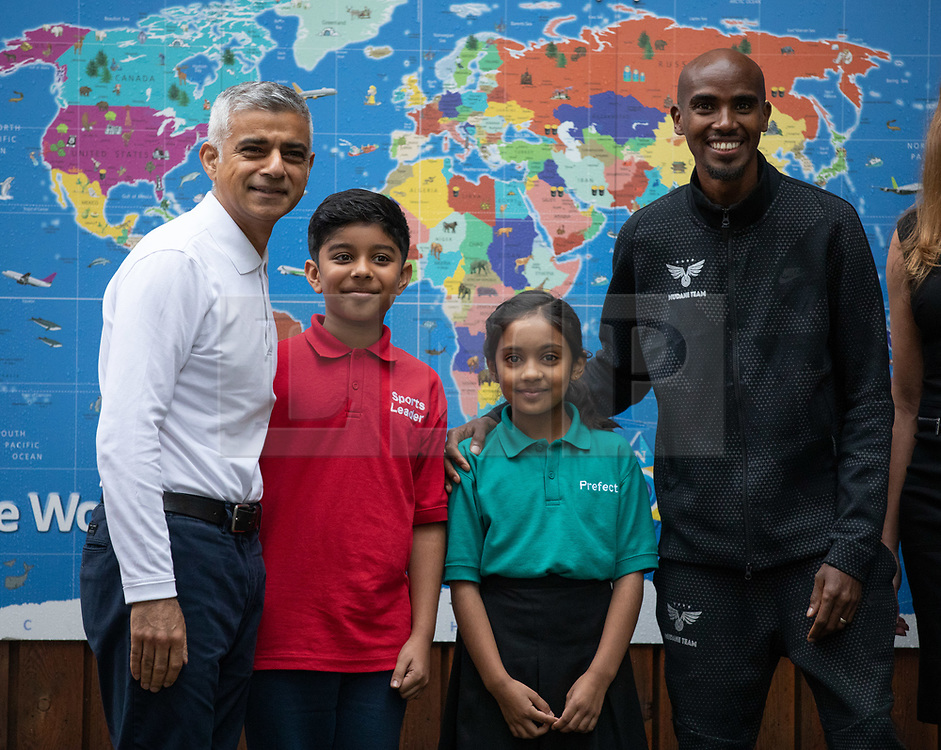© Licensed to London News Pictures. 15/10/2018. London, UK. Mayor of London Sadiq Khan (left) and British athlete Sir Mohamed Farah (right) with children from Cubitt Town Junior School launch a campaign to encourage London schools to take part in the Daily Mile initiative. The Daily Mile gets school children exercising outside for 15 minutes a day, to improve their physical, social, emotional and mental health and wellbeing. Photo credit : Tom Nicholson/LNP
