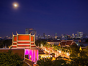 16 NOVEMBER 2013 - BANGKOK, THAILAND: The full moon rises over Bangkok during the annual temple fair at Wat Saket. Wat Saket is on a man-made hill in the historic section of Bangkok. The temple has golden spire that is 260 feet high which was the highest point in Bangkok for more than 100 years. The temple construction began in the 1800s in the reign of King Rama III and was completed in the reign of King Rama IV. The annual temple fair is held on the 12th lunar month, for nine days around the November full moon. During the fair a red cloth (reminiscent of a monk's robe) is placed around the Golden Mount while the temple grounds hosts Thai traditional theatre, food stalls and traditional shows.    PHOTO BY JACK KURTZ