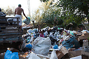 A young lady throws rubbish bags up to the back of a lorry at a recyling centre just outside Porte Alegre, Brazil. <br /> <br /> Cirandar is working in partnership with  C&A and C&A Instituto to implement a network of Community Libraries in eight communities of Porto Alegre.
