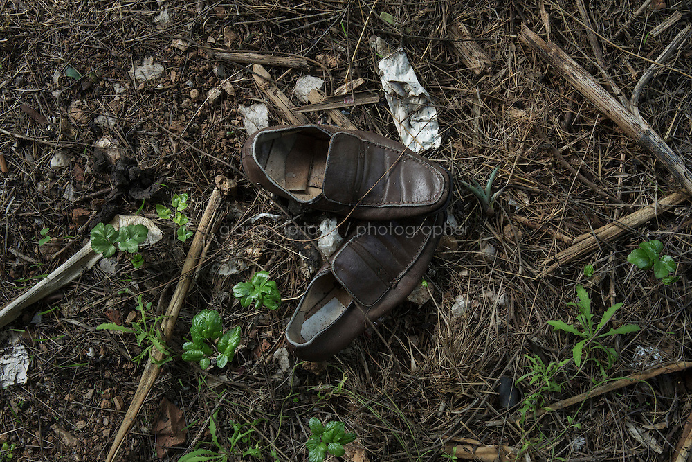 VENTIMIGLIA, ITALY - 20 NOVEMBER 2014: Shoes left by a migrant a trail near the Italian-French border  in Ventimiglia, Italy, on November 20th 2014.<br /> <br /> The Ventimiglia-Menton border is the border between Italy and France crossed by migrants who decide to continue their journey up north towards countries such as Germany, Sweden, The Netherlands and the UK where the process to receive the refugee status or humanitarian protection is smoother and faster. in Ventimiglia, Italy, on November 17th 2014.