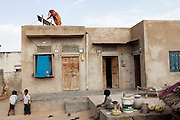 Santosh Devi, aged 19, climbs to the rooftop of her home, while dressed in a sari, to do some maintenance work on her solar panels. She graduated 2 years ago from the solar engineering course of the Barefoot College in Tilonia, Ajmer, Rajasthan, India. She has since solar powered 20 homes in her village, Balaji Ki Dhani, Bauli, Nagur District, Rajasthan, making it the first village in India to be 100% solar powered in all houses. Above this, she does all maintenance for the neighbouring village, Gudda Ki Dhani, where the previous male solar engineer had left the village to find unrelated work in the city. Barefoot College prefers training women to be solar engineers for this reason that they have higher chances of staying in the village instead of moving to the cities. Photo by Suzanne Lee for Panos London