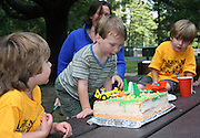 4 year old boys at birthday cake with cars decorations; celebration; outdoors; summer