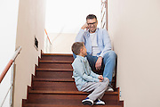 Happy father and son sitting on steps at home
