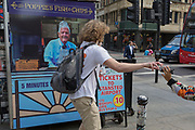 A young man stops to pick up a pair of sunglasses and hands them to a young woman near the rear of a newspaper vendor's kiosk outside Liverpool Street mainline station in the City of London - the capital's financial district, on 3rd September 2018, in London England.