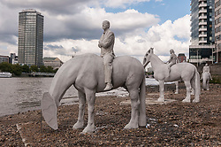 "© Licensed to London News Pictures. 02/09/2015 London, UK. The art installation entitled ""The Rising Tide"" (comprising four horse-riders on horses with petroleum pumps for heads) by the underwater eco-sculptor Jason deCaires Taylor, stands on the foreshore of the River Thames in Vauxhall and is revealed with each low tide.  The installation aims to question man's reliance on fossil fuels and is part of this year's Totally Thames festival. Photo credit : Stephen Chung/LNP"