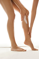 Woman Applying Body Lotion on Legs, Low Section