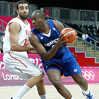 04 August 2012: France Ali Traore drives past Tunisia Makram Ben Romdhane during 73-69 Team France victory over Team Tunisia, during the men's basketball preliminary, at the Basketball Arena, in London, Great Britain.