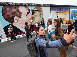 Tourist taking selfie photograph of mural painted on original section of Berlin Wall at East Side gallery in Berlin, Germany ...Editorial Use Only