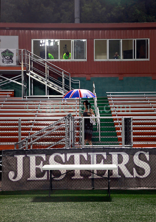 24 June 2015. New Orleans, Louisiana.<br /> National Premier Soccer League. NPSL. <br /> Jesters 0 - Atlanta Silverbacks 1.<br /> The New Orleans Jesters lose 0-1 to the Atlanta Silverbacks in a lightning delayed game at home in the Pan American Stadium. Lady in a Union Jack umbrella leaves the stands at the end of the game.<br /> Photo&copy;; Charlie Varley/varleypix.com