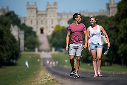 © Licensed to London News Pictures. 23/08/2016. Windsor, UK. A young couple enjoy the warm weather while walking along The Long Walk in front of Windsor Castle in Berkshire as temperatures in the south east hit 30 degrees. Photo credit: Ben Cawthra/LNP