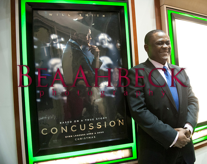 BEA AHBECK/NEWS-SENTINEL<br /> Forensic pathologist Dr. Bennet Omalu, who is portrayed in the movie Concussion by Will Smith, poses for a picture by the movie poster for the movie at Lodi Stadium 12 Cinemas during a fundraiser to benefit the San Joaquin County Family Justice Center Foundation in downtown Lodi Saturday evening, Jan. 9, 2016.