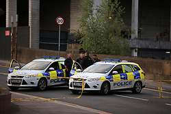 Police officers stand next to their vehicles near the Manchester Arena after a suspected terrorist attack at the end of a concert by US star Ariana Grande left 19 dead.