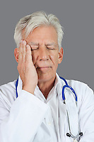 Senior doctor suffering from headache over gray background