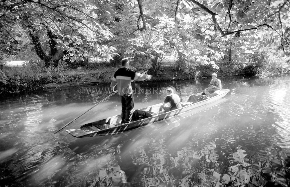Black and white photo of three men punting in Oxford, England.