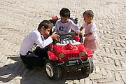 Uzbekistan, Khiva. Kids with toy pedal car.