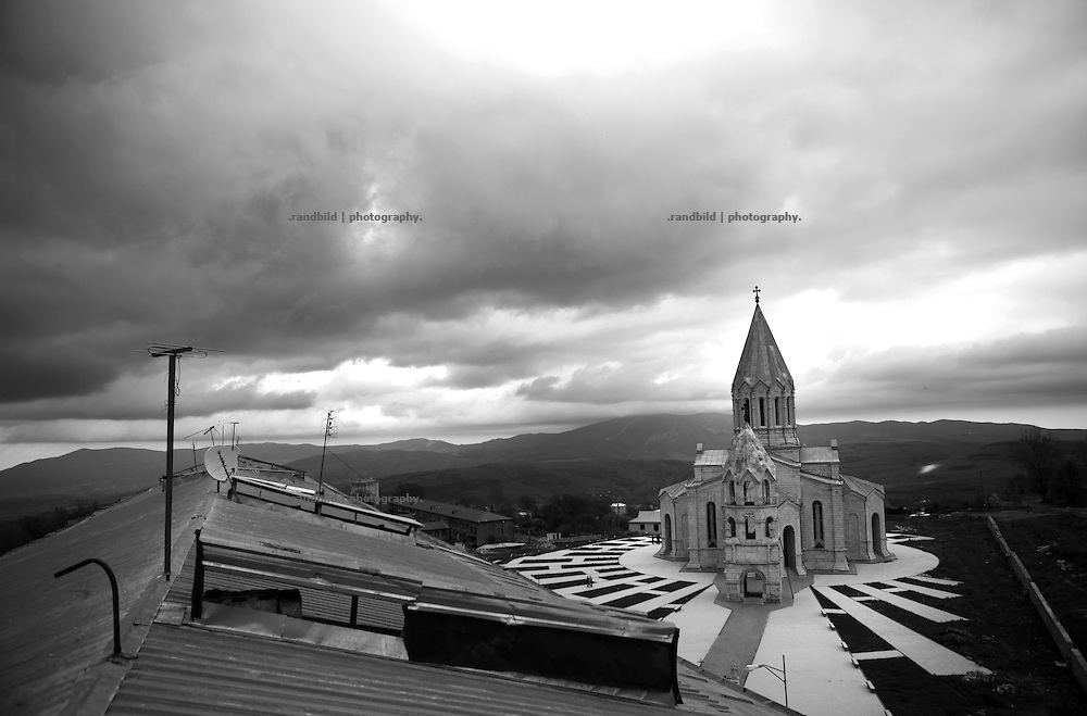 """A view down to Shushis Ghazanchetsots cathedral. This image is part of the photoproject """"The Twentieth Spring"""", a portrait of caucasian town Shushi 20 years after its so called """"Liberation"""" by armenian fighters. In its more than two centuries old history Shushi was ruled by different powers like armeniens, persians, russian or aseris. In 1991 a fierce battle for Karabakhs independence from Azerbaijan began. During the breakdown of Sowjet Union armenians didn´t want to stay within the Republic of Azerbaijan anymore. 1992 armenians manage to takeover """"ancient armenian Shushi"""" and pushed out remained aseris forces which had operate a rocket base there. Since then Shushi became an """"armenian town"""" again. Today, 20 yeras after statement of Karabakhs independence Shushi tries to find it´s opportunities for it´s future. The less populated town is still affected by devastation and ruins by it´s violent history. Life is mostly a daily struggle for the inhabitants to get expenses covered, caused by a lack of jobs and almost no perspective for a sustainable economic development. Shushi depends on donations by diaspora armenians. On the other hand those donations have made it possible to rebuild a cultural centre, recover new asphalt roads and other infrastructure. 20 years after Shushis fall into armenian hands Babies get born and people won´t never be under aseris rule again. The bloody early 1990´s civil war has moved into the trenches of the frontline 20 kilometer away from Shushi where it stuck since 1994. The karabakh conflict is still not solved and could turn to an open war every day. Nonetheless life goes on on the south caucasian rocky tip above mountainious region of Karabakh where Shushi enthrones ever since centuries."""