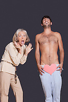 Shocked senior woman with young man holding red paper heart against black background