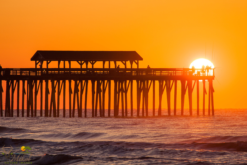 Myrtle Beach State Park pier with fisherman, sun rising behind