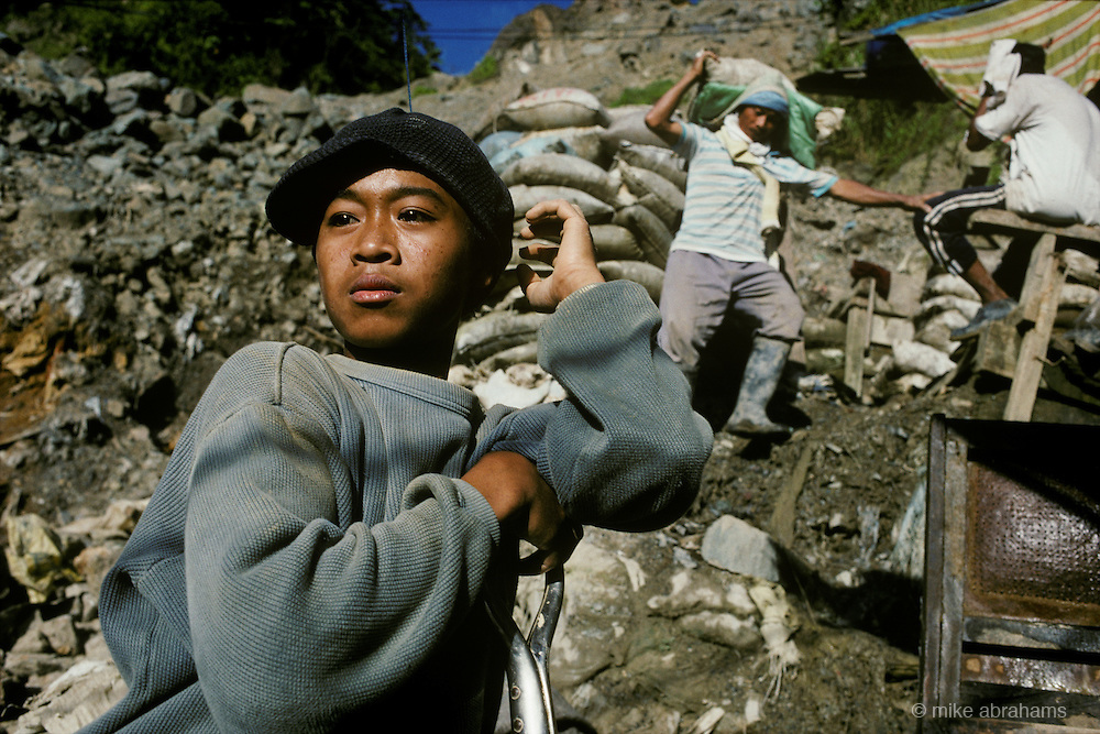 Child worker shovelling gold ore into a ball mill for processing. Mount Diwata, Mindanao, The Philippines