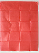 Red paper folded into a pattern of squares