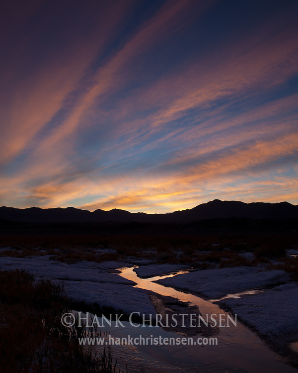 Sunrise clouds stream over seasonal rivulets, making their way through a valley of salt, Death Valley National Park