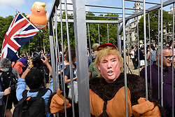 """© Licensed to London News Pictures. 13/07/2018. LONDON, UK.  A man dressed as Donald Trump as a gorilla stands in a cage outside The Houses of Parliament.  At the same time, a giant """"Trump Baby"""" balloon flies over Parliament Square in Westminster as part of a protest at President Donald Trump's visit to the UK.  Organisers have designed the 6m tall blimp, flying at a height of 30m,  depicting Donald Trump as a baby with small hands, holding a mobile phone and wearing a nappy.  Mass protests are also expected to take place in Central London in response to the visit of the President. Photo credit: Stephen Chung/LNP"""