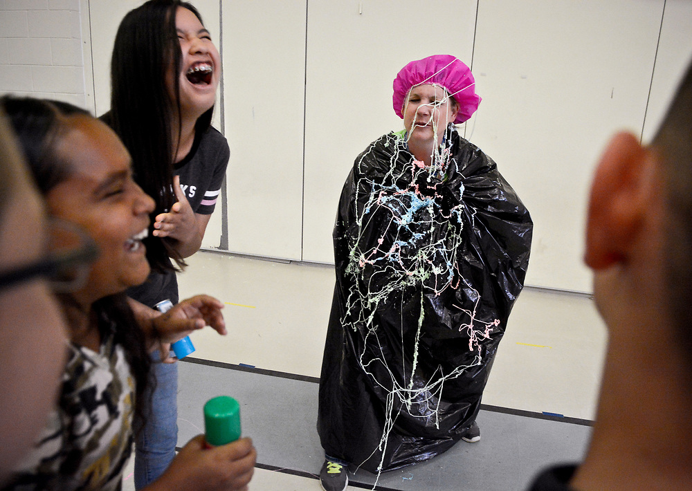 Cielo Azul teacher  Ryalin Hughes reacts after her students, including  SeungMena Conaway, top, and Destiny Herrera, second from left, aimed their silly string at her, Wednesday, May 17, 2017, at Cielo Azul Elementary in Rio Rancho, N.M. This was the first year that students who took the PARCC exams were given incentives: to smash a pie-in-face  or shoot silly string at a teacher or administrator. Kids who best followed the testing strategies were chosen. In total, about 18 pies were smashed in teachers' faces.  (Marla Brose/Albuquerque Journal)
