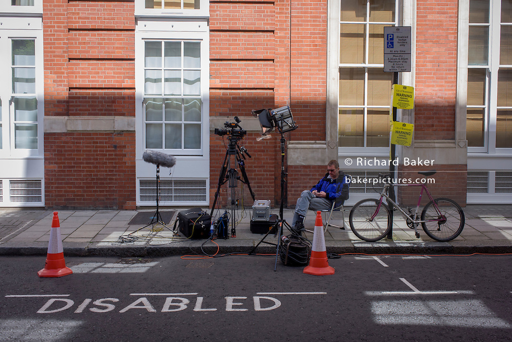 A TV technician awaits political coverage to gather pace outside Conservative Central Office, hours before the first results come in during the UK's 2015 election.