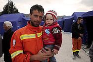7 Aprile 2009.Terremoto  Abruzzo.Il campo  degli  sfollati.Volontario con un bambino.Earthquak  Abruzzo.Tempera camp.Voluntary with a child .