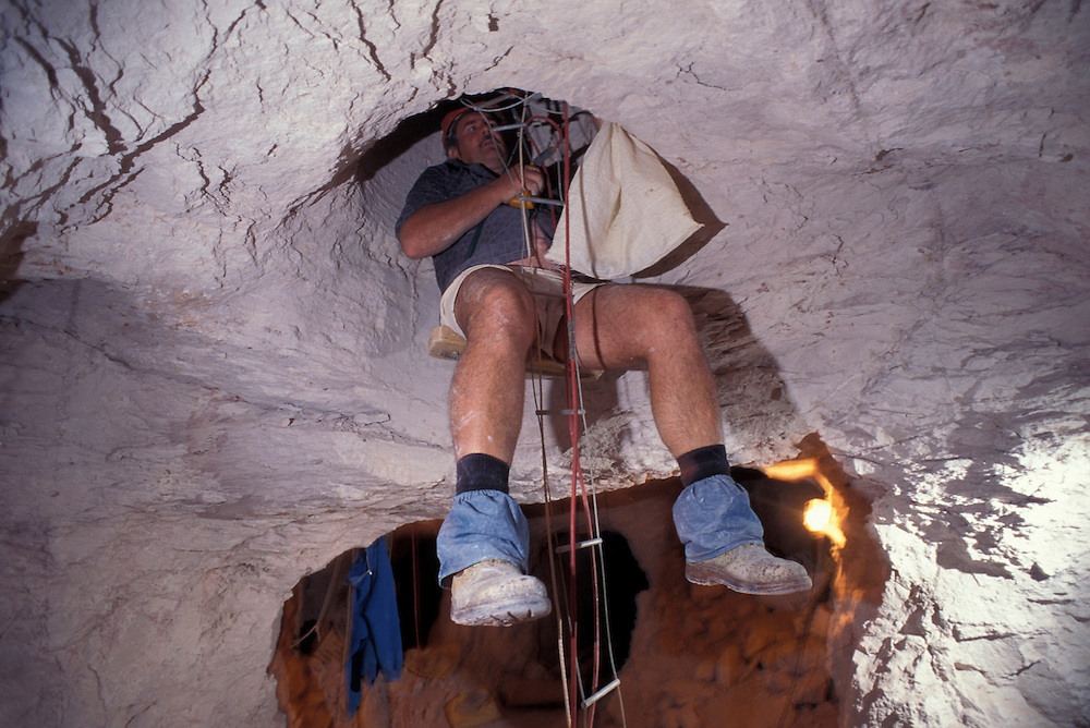 Australia, South Australia, (MR) Kary Aberhart lowers himself on winch into 100' deep opal mine shaft in Coober Pedy.